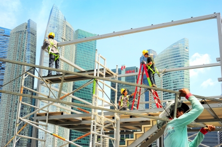 expected: Singapore, Republic of Singapore - May 09, 2013: Workers at construction site in front of Singapore downtown. Construction industry is expected to pull in some S$30 billion this year