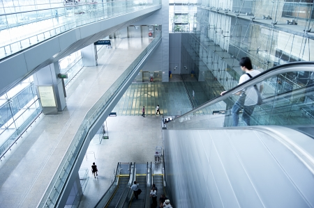 Singapore, Republic of Singapore - March 05, 2013 : People on escalators at Changi International Airport on  in Singapore. Changi Airport serves more than 100 airlines operating 6,100 weekly flights connecting Singapore to over 220 cities