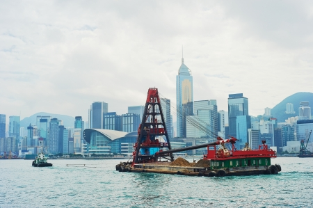tonnes: Barge in front of business district in Hong Kong. Some 456,000 vessels arrived in and departed from Hong Kong during the year, carrying 243 million tonnes of cargo  Stock Photo