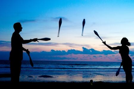 L'homme et la femme jonglant sur la plage de l'océan au coucher du soleil à Bali, Indonésie Banque d'images