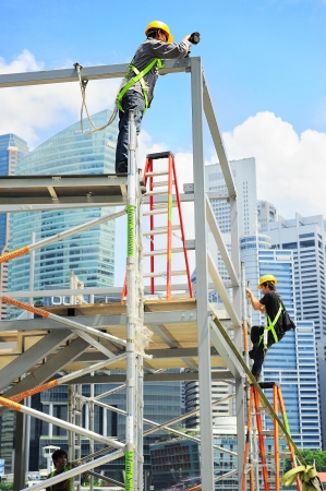 Singapore, Republic of Singapore - May 09, 2013: Workers at construction site in front of Singapore downtown. Construction industry is expected to pull in some S$30 billion this year