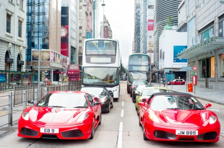 hk: Hong Kong, Hong Kong S.A.R. - May 19, 2013: Modern Ferarri cars on Nathan Rd in Hong Kong. Nathan Road is a main thoroughfare through Kowloon and is line with shops and restaurants.