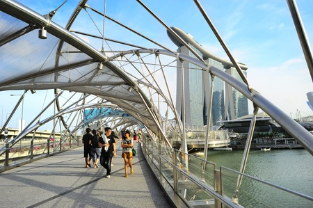 tonnes: Singapore, Republic of Singapore - May 03, 2013: People strolling on the Helix Bridge in Singapore. The Helix is fabricated from 650 tonnes of Duplex Stainless Steel and 1000 tonnes of carbon steel.