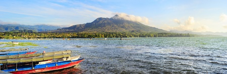 Fishing boats in front of volcano Batur at sunset photo