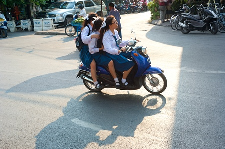 schoolgirl uniform: Chiang Mai, Thailand - Feb 27, 2013: Unidentified schoolgirls riding by motorbike in Chiang Mai, Thailand. Motorbike is the most popular and available transportation in South Asia.