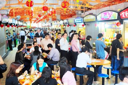 Singapore, Repubblica di Singapore - 6 MARZO 2013: La gente del posto mangia in una sala cibo popolare a Singapore. Bancarelle di cibo poco costoso sono numerosi in città, quindi la maggior parte di Singapore cenare fuori almeno una volta al giorno.