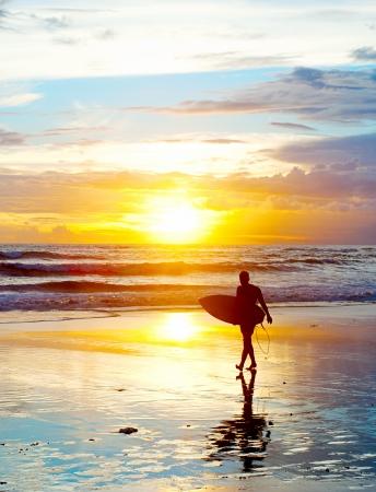 Surfer sulla spiaggia mare al tramonto sulla isola di Bali, Indonesia