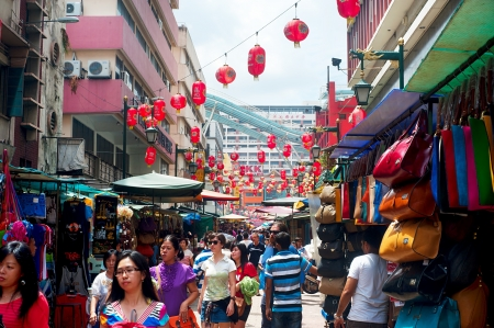 specializes: Kuala Lumpur, Malaysia - May 11, 2012: People walking on Petaling Street in Kuala Lumpur. The street is a long market which specializes in counterfeit clothes, watches and shoes. Famous tourist attraction Editorial