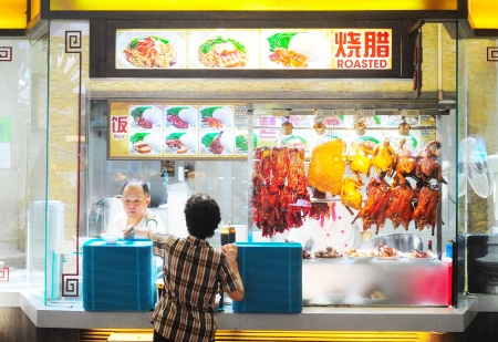 hawker: Singapore, Republic of Singapore - March 06, 2013: Food stall  in Singapore. Inexpensive food stalls are numerous in the city so most Singaporeans dine out at least once a day.