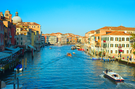 Tourists and locals chilling in cafe and touring Venice streets on boats enjoying the view photo