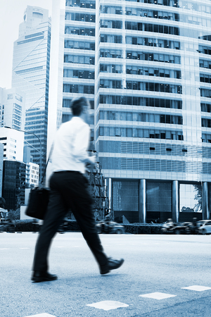 Unidentified businessman crossing the street in Singapore. There are more than 7,000 multinational corporations from US States, Japan and Europe in Singapore