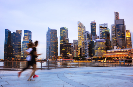 Two people jogging in front of Singapore downtown