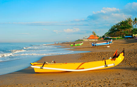 Balinese fisherman village at sunrise. Traditional Balinese fisherman boat on foreground photo