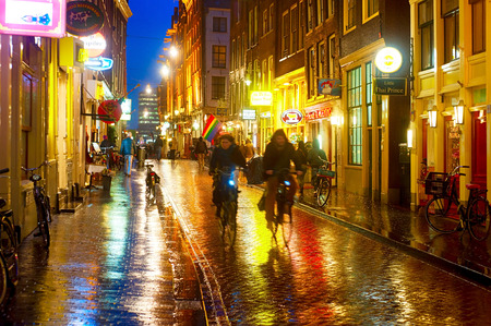 AMSTERDAM, NETHERLANDS - FEB 14, 2014: Unidentified people on the street of an old town of Amsterdam in the evening under the rain.