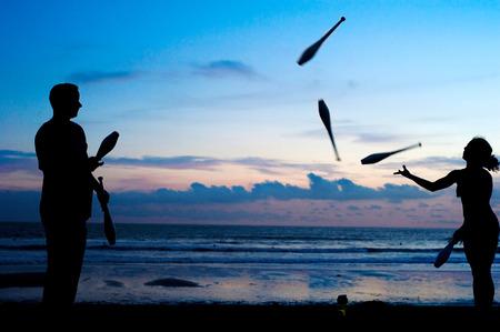 Les gens non identifiés jonglant sur la plage de l'océan au coucher du soleil. Bali, Indonesi Éditoriale