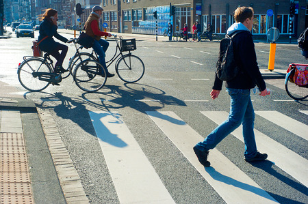 AMSTERDAM, NETHERLANDS - FEB 26, 2014: Unidentified people  crossing the street. It is one of the most cycle-friendly cities in the world. 58% of the citizens uses daily a bicycle.