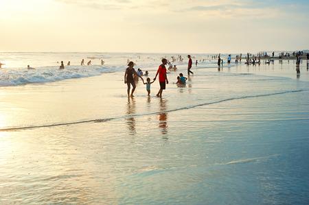 indonesisch: Kuta, Bali eiland, Indonesië - 17 maart 2013: lokale mensen die rust op de oceaan strand op Bali eiland. Met een bevolking van urrently 4.220.000, het eiland is de thuisbasis van de meeste van de Hindoe minderheid van Indonesië.