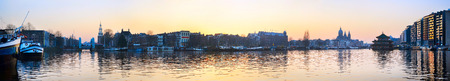 Panorama of Amsterdam old town with reflection in Amstel river photo