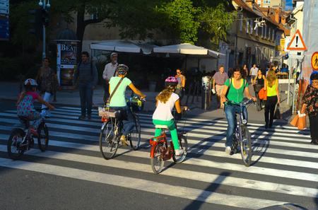 LUJBLJANA, SLOVENIA - SEPTEMBER 9, 2013: Unidentified people crossing street and riding bicycles on the street of Ljubljana. The downtown quarter usually attracts lots of tourists.