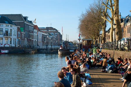 dutch girl: UTRECHT, NETHERLANDS - MARCH 09, 2014: People relaxing in the sun by a river canal in central Utrecht. Utrecht  is the capital and most populous city in the Dutch province of Utrecht