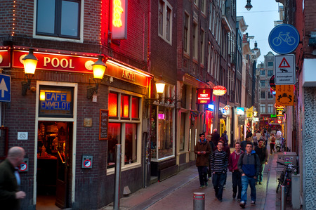 AMSTERDAM, NETHERLANDS - MARCH 10, 2014: People at Old Town street in Amsterdam. Amsterdam is the capital city of and the most populous within the Kingdom of the Netherlands