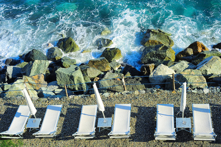 Deck chair at a rocky beach. Mediterranean sea, Italy photo