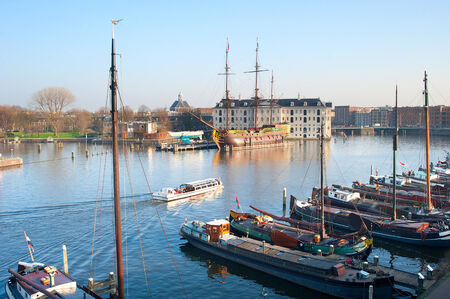 amstel river: Water excursion by the Amstel river in Amsterdam, Netherlands. National Maritime Museum in the background