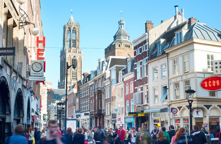UTRECHT, NETHERLANDS - MARCH 03, 2014:: People walking on the old town street, in front of the Dom Tower. Cathedral (Dom) tower is the symbol of the city and the tallest church tower in Netherlands.