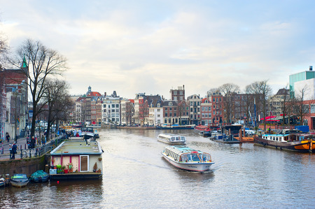 almost all: AMSTERDAM, NETHERLANDS - MARCH 17, 2014: Tourist boat cruises on canal  in Amsterdam. Almost 20 percent of all canal cruise boats are now electrically powered Editorial