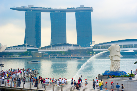 SINGAPORE - MAY 09, 2013: Tourists at the Merlion fountain in\ front of the Marina Bay Sands hotel in Singapore. Merlion is a\ imaginary creature with the head of a lion, seen as a symbol of\ Singapore\