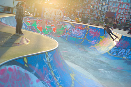 well equipped: AMSTERDAM, THE NETHERLANDS – FEBRUARY 24, 2014: Local skaters are training on a skate ground in Amsterdam on a warm winter day. Residential districts are well equipped for sport activities there.