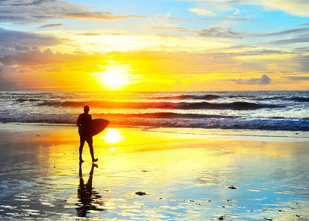 Surfer walking with surfboard on the ocean beach at sunset. Bali island, Indonesia  Standard-Bild