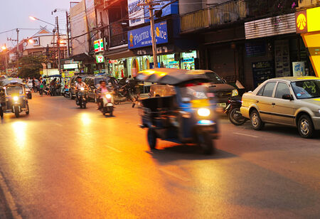 culturally: CHIANG MAI, THAILAND - FEB 26, 2013: Busy traffic on a road at dusk in Chiang Mai. Chiang Mai is the largest and most culturally significant city in northern Thailand