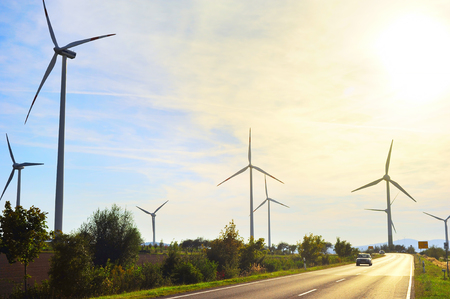 energy fields: Power wing turbines and road in Germany at sunset Stock Photo