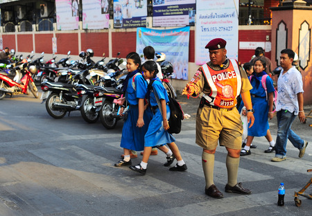one lane road sign: CHIANG MAI, THAILAND - FEB 27, 2013: Young policeman at work in Chiang Mai. Chiang Mai is the largest and most culturally significant city in northern Thailand.