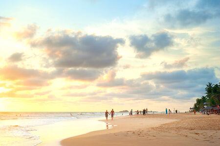 People walking on the beach of Sri Lanka at sunset photo