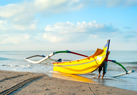 Local fisherman carrying a boat to the ocean. Bali island, Indonesia photo