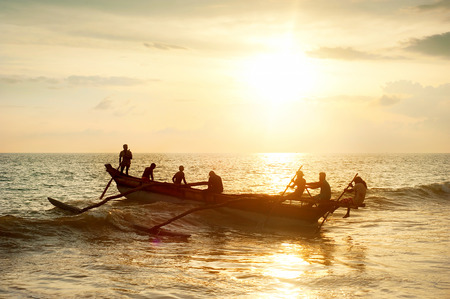 Firsherman on a boat in the ocean at sunset in Sri Lanka photo