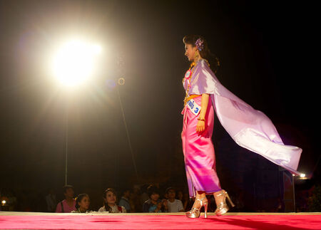 defile: LOPBURI, THAILAND - FEB 23, 2013: Model in traditional Thailand dress walking on a stage during the land of King Narai festival.