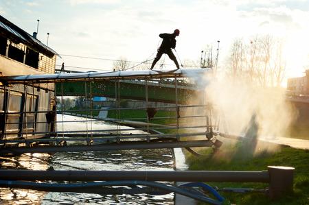 power boat: Man cleaning floating restaurant in Krakow, Poland  Stock Photo