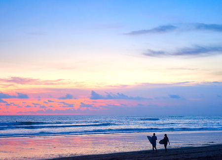 Couple of surfers walking on the beach on Bali island, Indonesia photo
