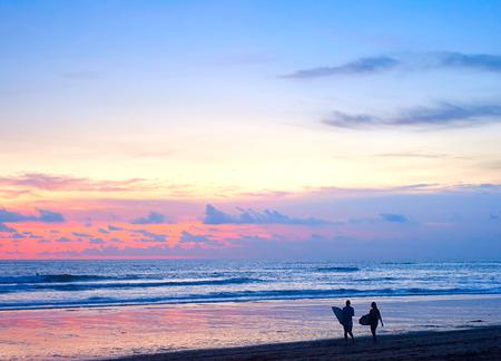 Couple of surfers walking on the beach on Bali island, Indonesia