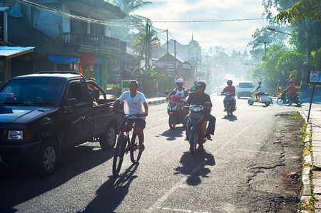 adult indonesia: UBUD, BALI ISLAND, INDONESAI - MARCH 14, 2013: Traffic on the Ubud road during rush hour. Ubud is one of Balis major arts and culture centres, it has developed a large tourism industry