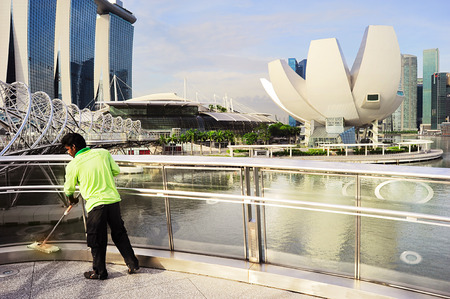 tonnes: SINGAPORE- MAY 07, 2013: Worker cleaning the Helix bridge in front of Singapore downtown. The Helix is fabricated from 650 tonnes of Duplex Stainless Steel and 1000 tonnes of carbon steel.