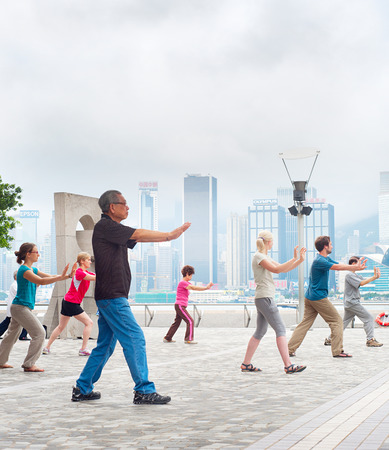 HONG KONG - MAY 15, 2013: Tai Chi Public Exercising in early morning  in Hong Kong. With a land of 1,104 km and population of 7 million, Hong Kong is one of the most densely populated areas in the world