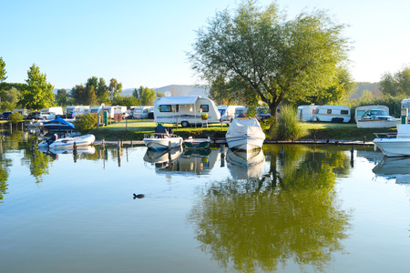 Camping site on a lake with caravans and boats