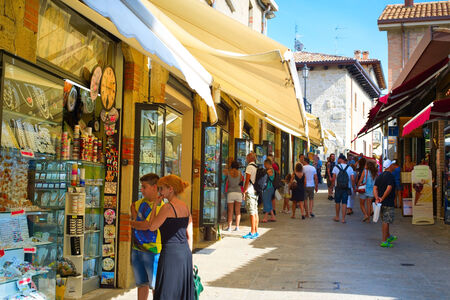 contributes: SAN MARINO - AUGUST 11, 2014: Tourists at the street of Old Town of San Marino. Tourism in San Marino contributes approximately 2.2% of San Marinos GDP.