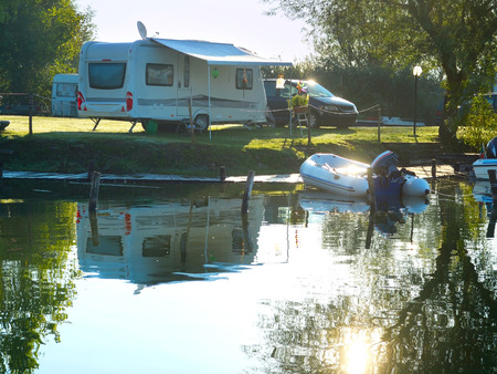 site: Camping site on a lake with caravans and boats