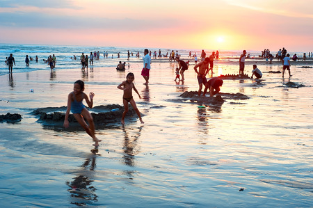 KUTA, BALI ISLAND, INDONESIA - MARCH 17, 2013: Local people resting at the ocean beach on Bali island. With a population of currently 4.22 million, island is home to most of Indonesias Hindu minority