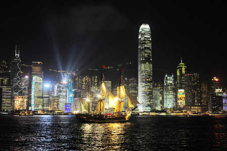 Victoria harbor with famous traditional Chinese junk at night. Hong Kong photo